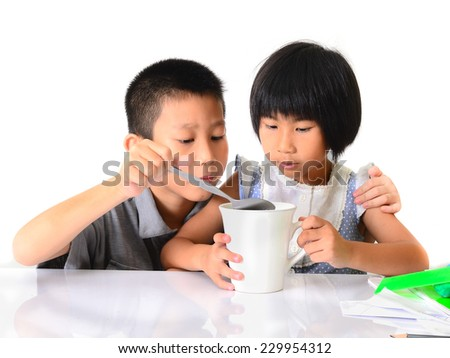 Asian children making some drink at home.