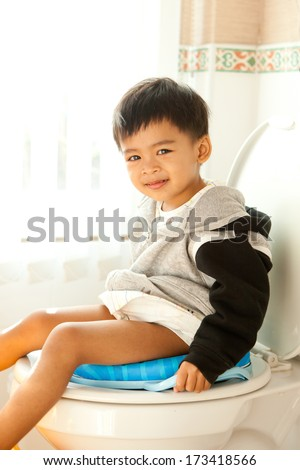 Asian children siting on toilet seat - stock photo