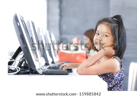 Asian children to using computer in classroom - stock photo