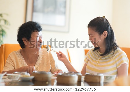 Asian Chinese adult daughter feeding her senior parent food - stock photo