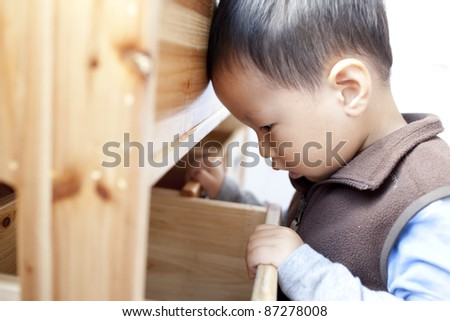 Asian chinese boy opening a  drawer
