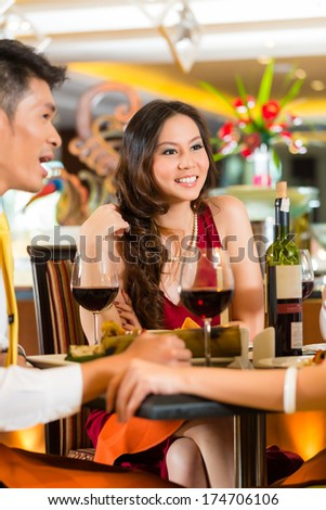 Asian Chinese business people having dinner in elegant club restaurant or hotel - stock photo