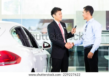 Asian Chinese Car Salesman selling auto to customer - stock photo
