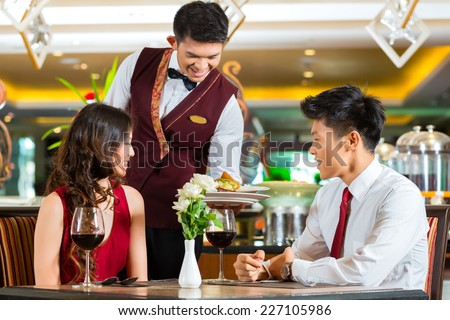 Asian Chinese couple - Man and woman - or lovers having a date or romantic dinner in a fancy restaurant while the waiter is serving food - stock photo