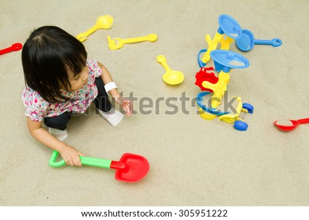 Asian Chinese little girl playing sand at indoor playground. - stock photo