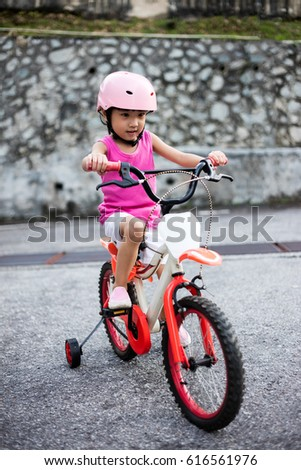 Asian Chinese little girl riding bicycle on tar road outdoor.