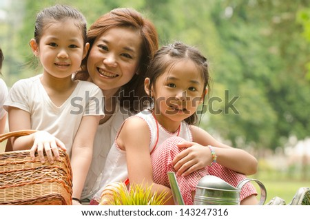 asian chinese mother and her daughters on the park - stock photo