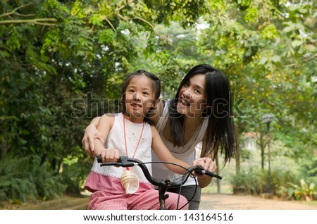 asian chinese mother teaching her daughter riding bicycle outdoor - stock photo