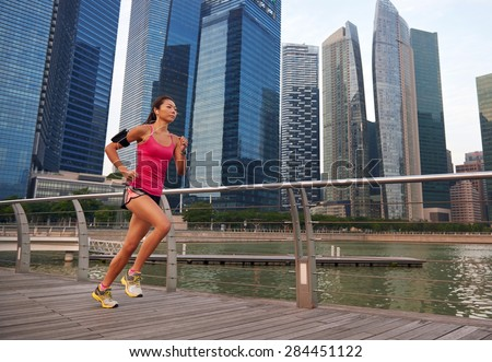 asian chinese sporty running woman working out running outdoors along urban city harbor sidewalk morning