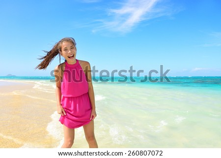 Asian Chinese tourist woman having fun on beach. Young mixed race female adult playing in water wearing pink halter sundress laughing during summer travel holidays. Tropical sunny destination. - stock photo