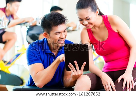 Asian Chinese Woman and personal fitness trainer in gym discussing training schedule and goals for workout  - stock photo