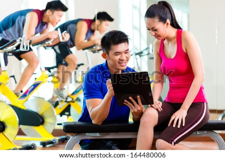 Asian Chinese Woman and personal fitness trainer in gym discussing training schedule and goals for workout