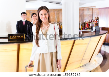 Asian Chinese woman arriving at front desk of luxury hotel in business clothes with trolley - stock photo
