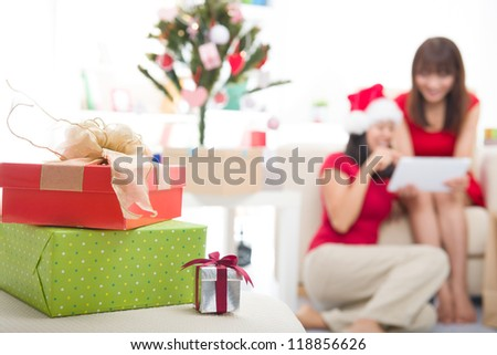 asian christmas friends doing online shopping candid photo,focus on front