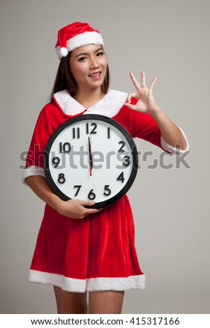 Asian Christmas girl in Santa Claus clothes and clock at midnight  on gray background