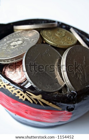 Asian coins in a miniature basket of wealth. - stock photo