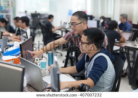Asian Colleagues Software Developers Team Sitting At Desk Working Laptop Computer Business People Group Real Office - stock photo