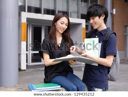 Asian college couple student sitting holding laptop on campus - stock photo