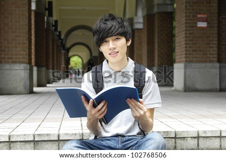 Asian college student sitting student reading on campus - stock photo