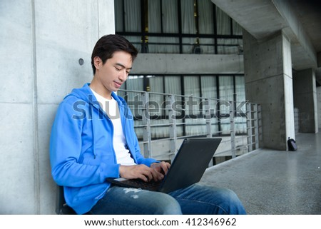 Asian college student sitting with laptop on campus