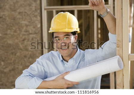 Asian construction worker holding blueprints - stock photo