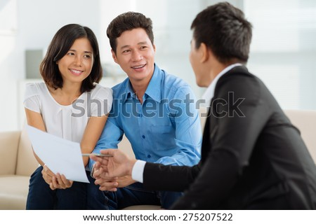 Asian couple at financial planning consultation - stock photo
