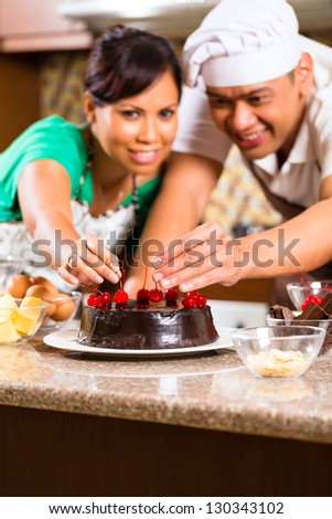Asian couple baking homemade chocolate cake with cherries  in their kitchen for dessert
