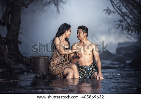 Asian couple bathing at cascade (Vintage color) - stock photo