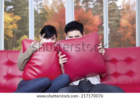 Asian couple covering their face while watching horror movie at home in autumn - stock photo