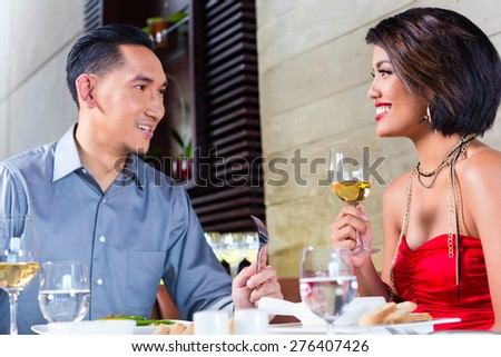 Asian couple having dinner and drinking red wine in very fancy restaurant  - stock photo