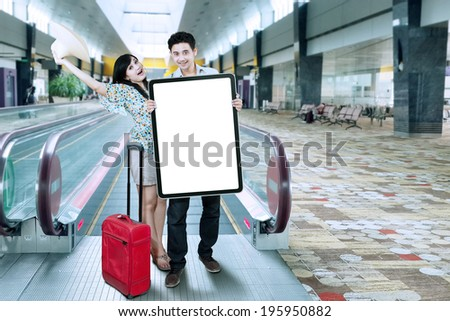 Asian couple hold blank board in the airport hall - stock photo