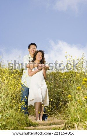Asian couple hugging in field - stock photo