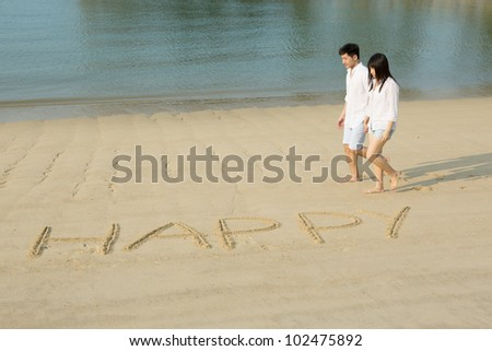 Asian couple in love walking on the beach with the word 'Happy' drawn in the sand. - stock photo
