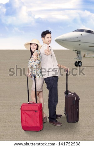 Asian couple is traveling by airplane, carrying suitcases at the airport - stock photo