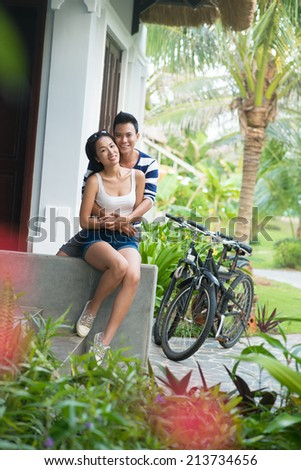 Asian couple on the porch: man hugging his girlfriend from behind - stock photo