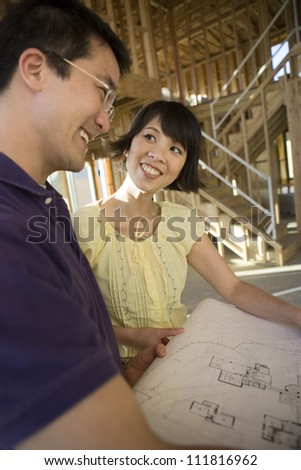 Asian couple reviewing blueprint at construction site - stock photo