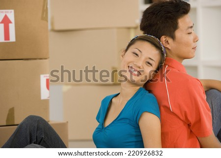 Asian couple sitting back to back next to moving boxes - stock photo