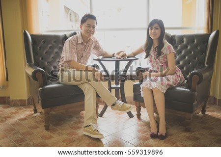 asian couple sitting on black couches in front of light glasses in a room