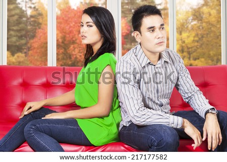 Asian couple sitting separately on sofa after quarreling at home - stock photo