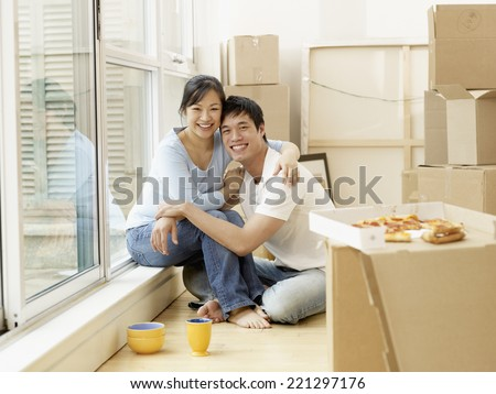 Asian couple surrounded by moving boxes - stock photo