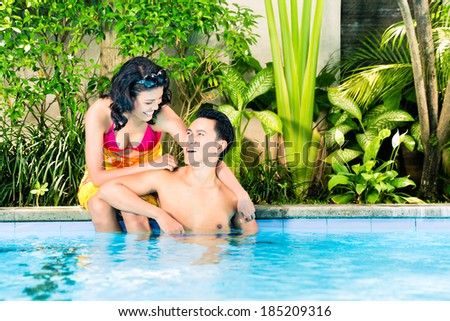 Asian couple swimming in hotel or club pool - stock photo