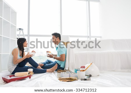 Asian couple talking and eating instant noodle after moving to new house - stock photo