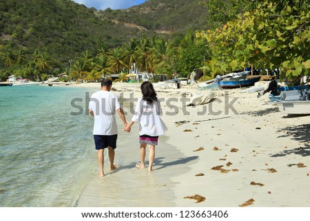 Asian couple walking on a beach, holding hands - stock photo