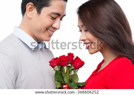 Asian couple with flowers. Portrait of smiling couple embracing on white background - stock photo