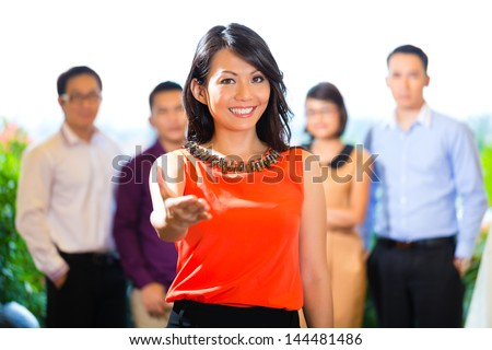 Asian Creative team - young businesspeople are successful with a project greeting a new team member - stock photo