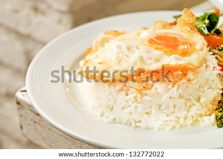 Asian cuisine, a fried egg on rice, chicken with Basil Stir Fry. - stock photo
