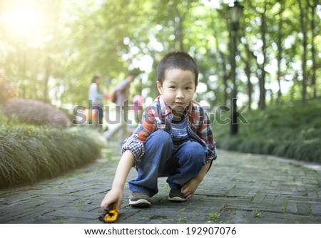 Asian cute boy playing car toy on grassland - stock photo
