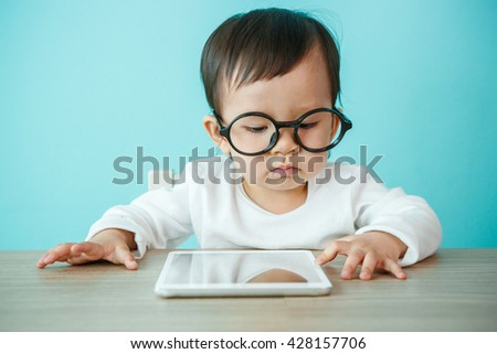 Asian Cute caucasian baby using digital tablet on the blue background - stock photo
