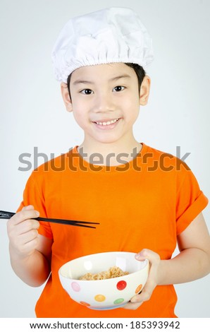 Asian cute child eating ramen noodles in ceramic bowl . - stock photo