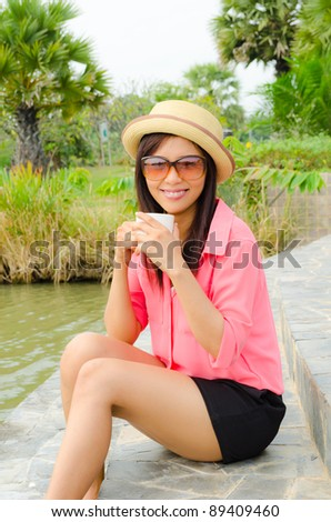 Asian cute girl drinking coffee in park